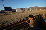 TIJUANA, MEX-OCT12: Melanie Rodriguez stands with her doll at the U.S.-Mexico border overlooking border wall prototypes under construction on Thursday, October 12, 2017 in Tijuana, Mexico.  Border wall  prototypes proposed by President Donald Trump are starting to take shape on Otay Mesa in San Diego County, just north of the U.S.-Mexico border. Competitors who are hoping to gain approval to build the wall have until the first of next month to complete their work.(Photo by Sandy Huffaker/