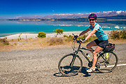 Cyclist riding along the Lake Pukaki under the Southern Alps, Canterbury, South Island, New Zealand