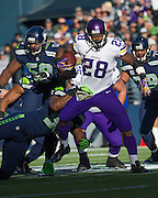 Minnesota Vikings running back, Adrian Peterson attempts to break a tackle in a game against the Seattle Seahawks. Photo by John Lill.