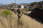 Nogales, Arizona, USA.  24th November, 2018.  A soldier stands watch U.S. Army troops installing barbed wire on the U.S./Mexico border wall west of the DeConcini Port of Entry as part of Operation Secure Line in Nogales, Arizona, USA. 7,000 soldiers were deployed to the southwestern U.S. border last month at the request of President Donald Trump's administration.