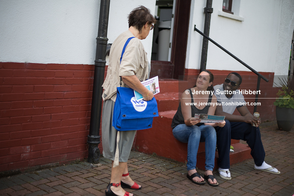 Carole Ford (standing), a Pro-Union Better Together supporter out leafletting, talks to a family in their garden, ahead of the Scottish referendum vote on independence, in Pollok district, Glasgow, Scotland, Thursday 26th June 2014.