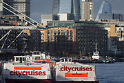 Three 'Thames City Cruises' tour boats are moored downriver from the former warehouses of Butler's Wharf on the river Thames, on 17th January 2020, in London, England.
