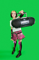 Portrait of young woman holding boom box over green background