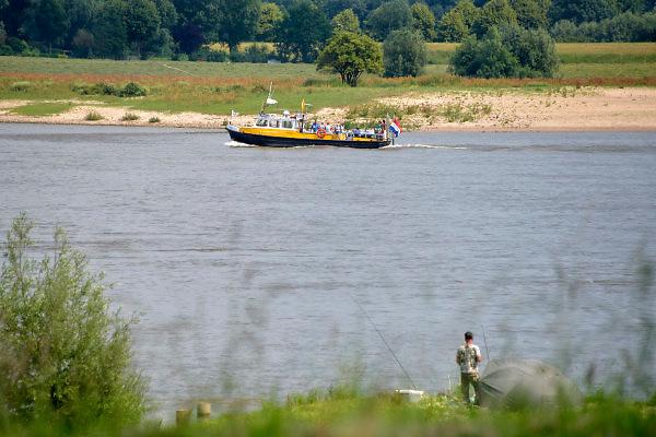 Nederland, Varik, 9-6-2018In dit deel van de Waal zijn de kribben verlaagd of vervangen door langsliggende dammen om de waterafvoer te verbeteren . Het fietsveer, voetgangerspontje, vaart aan de overkantFoto: Flip Franssen