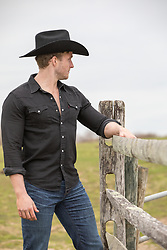 back of a cowboy looking out to a ranch hot cowboy by a rustic fence on a ranch