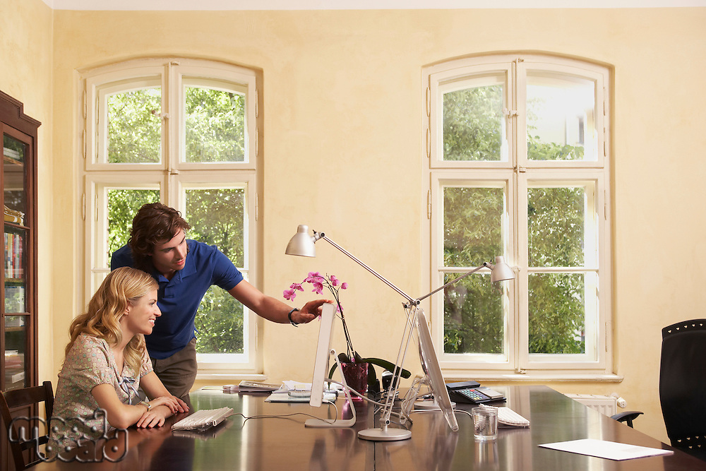 Young man helping young woman working on computer in living room