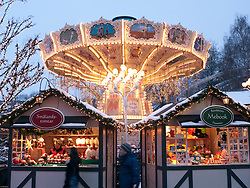 Funfair and small wooden craft shops at dusk at Christmas market in Liseberg amusement park in Gothenburg Sweden