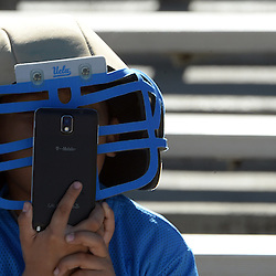 A UCLA fans looks at his phone while wearing a UCLA helmet prior to a NCAA college football game against Stanford at the Rose Bowl in Pasadena, Calif., Friday, Nov. 28, 2014.