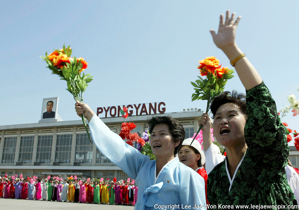 North Koreans wave flowers as South Koreans arrive at Sunahn airport in North Korea's capital Pyongyang. Photo by Lee Jae-Won (NORTH KOREA) www.leejaewonpix.com/