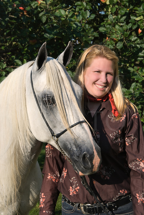 Stock photo of an Arabian horse owner and her beautiful white stallion with long forelock.