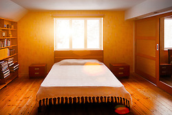 Bedroom interior with large bed, furniture, wooden floor and bedside tabel. Window, sun, sunflare. Flare
