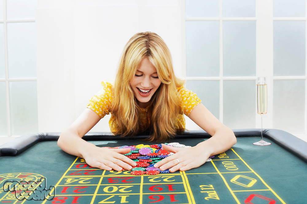 Happy woman at roulette table collecting chips