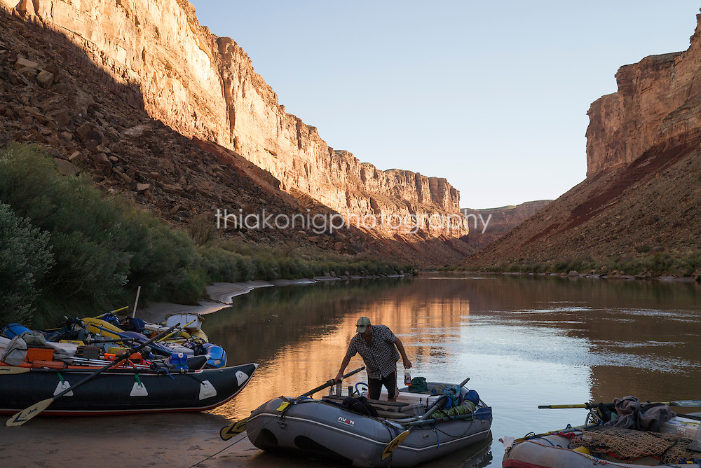 A boatman gathers supplies for dinner from boat cooler, Grand Canyon, AZ
