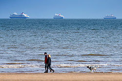 Portobello, Scotland, UK. 28 March, 2020. On the first weekend of the coronavirus lockdown the public were outdoors exercising and maintaining social distancing along Portobello beachfront promenade. Pictured People walking dog on beach with three cruise ships berthed in distance. Iain Masterton/Alamy Live News