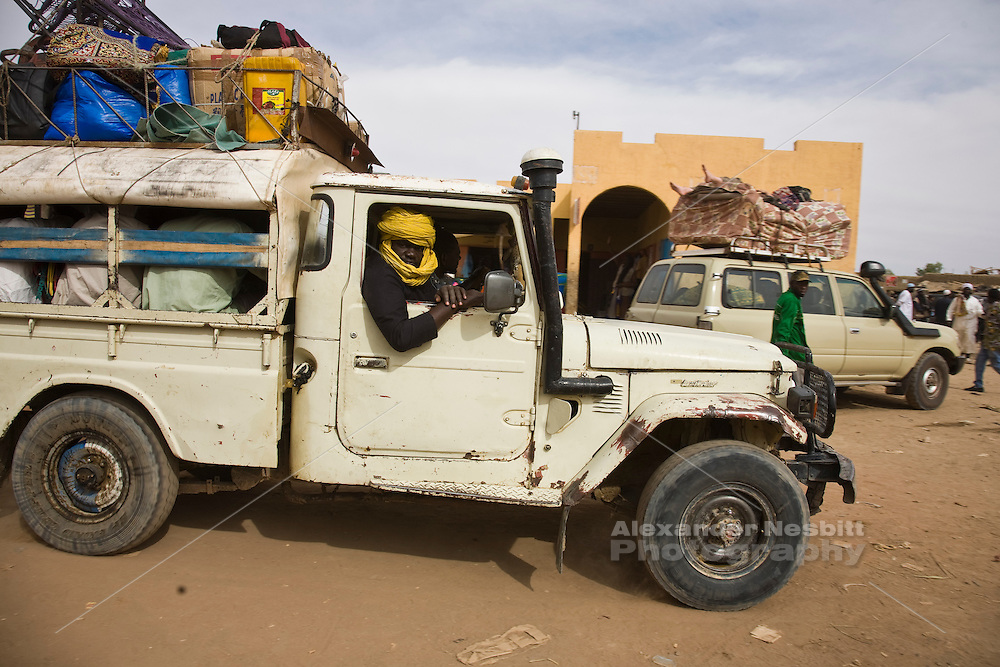 Korioume, Mali 2009 -       A Tuareg man eyes the camera from the front of a Land Cruiser pickup truck, as it waits in a traffic jam for the ferry to cross the Niger River headed south from Timbuktu to Douentza. The truck is transporting passengers as well as goods.