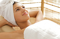 Close-up of young woman relaxing on massage table with hands behind head