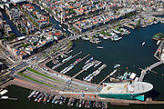 Nederland, Amsterdam, Oosterdok, 12-05-2009; Oosterdok met wetenschapsmuseum NeMo. In het water van het Oosterdok woonschepen, aan de steigers schepen voor de recreatievaart. Links de Prins Hendrikkade (PH-kade) en de Oude Schans met Montelbaanstoren en zicht op de Nieuwmarktbuurt Swart collectie, luchtfoto (toeslag); Swart Collection, aerial photo (additional fee required).foto Siebe Swart / photo Siebe Swart