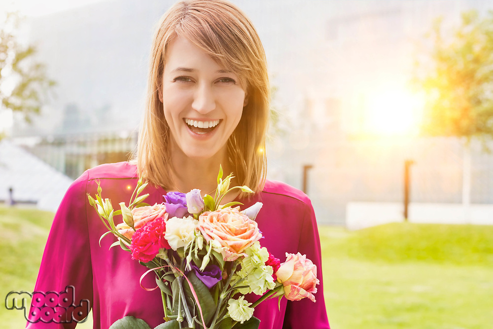 Portrait of young attractive woman holding boquet of flowers