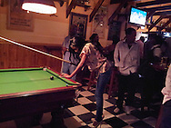 Harare, Zimbabwe. November, 2012. a bar patron lies up a shot in a pool game. She was an excellent player.