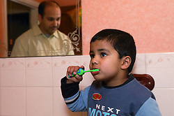 Young boy brushing his teeth with his father looking on; reflected in the mirror,