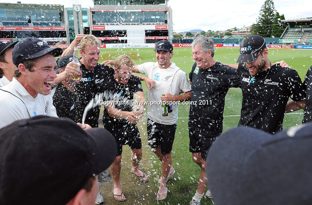 Tim Southee gets the champagne out in the middle of the wicket ater a famous victory over Australia on Day 4 of the second cricket test between Australia and New Zealand Black Caps at Bellerive Oval in Hobart, Monday 12 December 2011. Photo: Andrew Cornaga/Photosport.co.nz