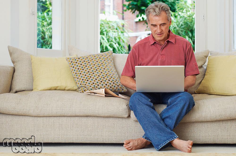 Man using laptop sat on sofa
