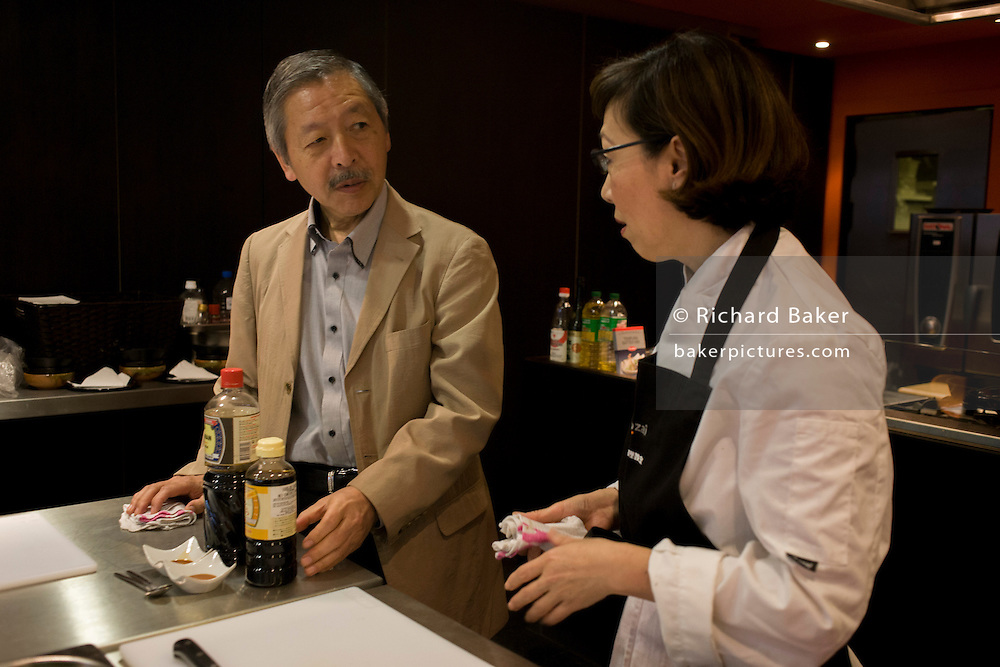 Japanese-born entrepreneur, Tetsuro Hama talks to his employee, a teacher at his food school in the City of London.
