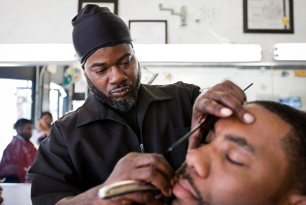 MILWAUKEE, WI - NOVEMBER 17: Cedric Fleming, left, cuts the hair of a customer at Upper Cutz barbershop on Thursday, November 17, 2016.