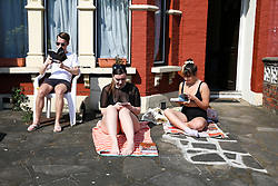 © Licensed to London News Pictures. 10/04/2020. London, UK. Members of public are seen reading in their front garden in north London on a warm and sunny Good Friday, during the outbreak of the COVID-19 virus. The government has urged Britons not to go out during the Easter holiday weekend despite the warm weather, to reduce the spread of coronavirus. Britain's coronavirus death rate goes up by 953 to 8,931. Photo credit: Dinendra Haria/LNP