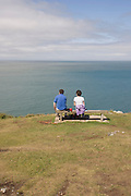 A walking couple rest on a bench at Morte Point on the North Devon Coast.