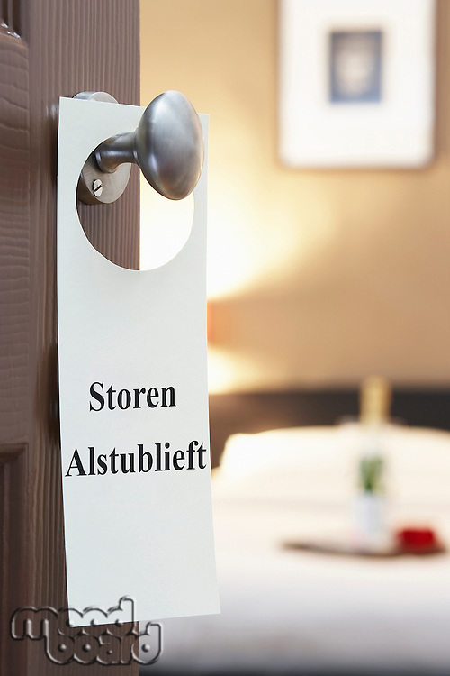 Sign with Dutch text hanging on hotel room door
