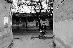 Man cycling through maze of hutongs or alleyways in Beijing China