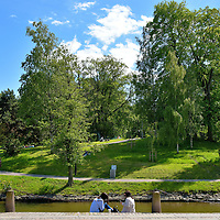 Women Across From King&rsquo;s Park in Gothenburg, Sweden<br /> After the fortified walls around Gothenburg were dismantled in the early 1800s, the surrounding moats were converted into channels.  These two women are sitting along a quay on the Rosenlund Canal. Across from them is Kungsparken.  At 32.5 acres, King&rsquo;s Park is one of the city&rsquo;s largest green spaces.