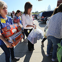 Susan Meredith, from left, Andi Hildenbrand and Debbie Banko help unload a van loaded with food to help fill the food pantry at Tupelo High School.