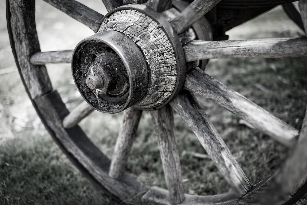 Black and white photo of and old and rusted wagon wheel.
