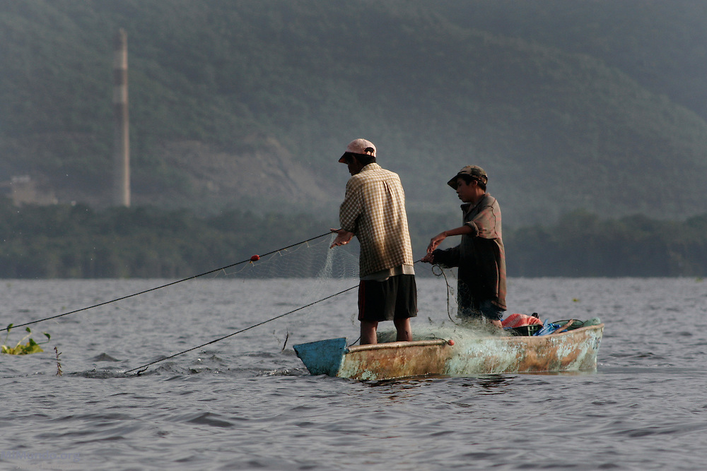 Local fishermen fish in Guatemala's largest fresh water body, Lake Izabal. A natural reserve and home to dozens of lakeside Q'eqchi' Mayan communities, lake izabal is threatened by a Canadian-owned nickel mine ran by the Guatemalan Nickel Company. The controversial mine, pictured in the background, began operations in the 1960 but remained closed for more of its original 40-year concession.