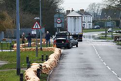 © Licensed to London News Pictures. 10/02/2014. Datchet, Berkshire, UK. A man and woman taking sandbags from a constructed flood defence. Flooding in Datchet today, 10th February 2014 after the River Thames burst its banks. Photo credit : Rob Arnold/LNP