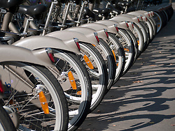 row of parked public  rental bicycles called Velib on Paris street in France