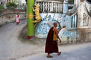 A buddhist monk passes the entrance to a nunnery in Sagaing.<br /> <br /> Sagaing became the short-lived capital of the independent Shan kingdom around 1,315, after the fall of Bagan had thrown central Myanmar into chaos.<br /> <br /> It is now mostly known as a religious center of dozens of Buddhist monasteries and nunneries.