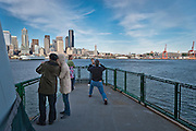 Tourists pose for photos on board a ferry arriving in Seattle in Elliot Bay of Puget Sound, WA, USA