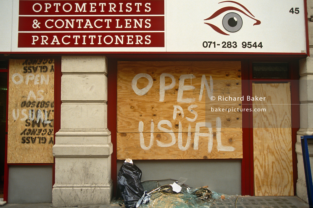 Two days after the Irish Republican Army (IRA) exploded a truck bomb on Bishopsgate, an optometrist's business remains open (like the eye illustration at the frontage) but it is boarded up with plywood with the words Open as Usual painted by hand. Debris has been swept up on the pavement awaiting collection but the scene is otherwise as it should. But one person was killed when the one-ton fertiliser bomb detonated directly outside the medieval St Ethelburga's church on 24th April 1993. Buildings up to 500 metres away were damaged, with one and a half million square feet (140,000 m) of office and retail space being affected and over 500 tonnes of glass broken. Costs of repairing the damage was estimated at £350 million. It was possibly the (IRA's) most successful military tactic since the start of the Troubles.