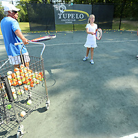 Omar Alcaino, Tupelo Junior Tennis Team Coach, pulls a hopper of tennis balls over for hitting practice with Catherine Gillon and Colbie O'Rear during practice Thursday afternoon at the Tupelo Country Club. The team has advanced to the USTA Southern Sectionals.
