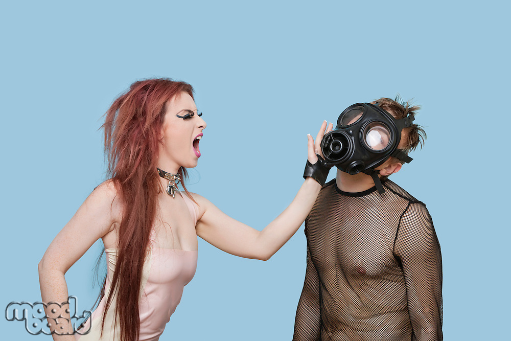 Funky young woman slapping man in gas mask over blue background