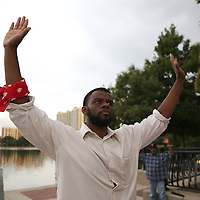 "DeQuan Shanks leads protesters in raising their arms at Lake Eola park during the ""National Moment of Silence"" event at the Lake Eola bandshell in downtown Orlando, Florida on Thursday, August 14, 2014. In light of the recent killing of eighteen year old Mike Brown in Ferguson, Missouri, citizens across America are gathering in solidarity to hold vigils and observe a moment of silence to honor victims of suspected police brutality. (AP Photo/Alex Menendez)"