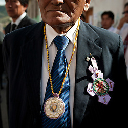 Juan Flores Rojas, a member of a religious brotherhood (Hermandad de Culto a Jesus Nazareno y la Virgen Dolorosa), wears the brotherhood's insignias as he waits for the beginning of a procession on Tuesday in Ayacucho, Peru.