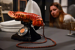 """© Licensed to London News Pictures. 03/10/2017. London, UK.  A staff member views (L to R) """"Fountain, 1917"""", 1964 edition, by Michel Duchamp and """"Lobster Telephone (red)"""", 1938, by Salvador Dali with Edward James at the preview of """"Dali / Duchamp"""", a new exhibition of works by Salvador Dali and Michel Duchamp taking place at the Royal Academy of Arts in Piccadilly.  Over 80 artworks in different media are on display from 7 October to 3 January 2018.   Photo credit : Stephen Chung/LNP"""