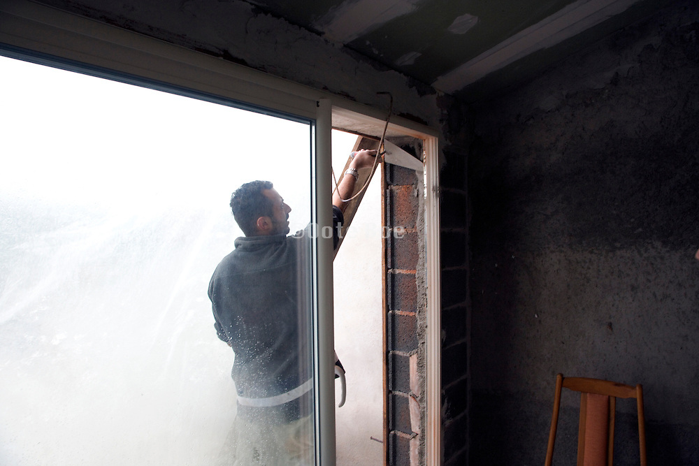 construction worker cementing a window pane