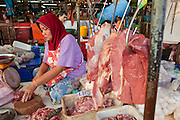 Sept. 23, 2009 -- BANGKOK, THAILAND: A Muslim woman sells beef in Khlong Toey Market in Bangkok, Thailand. Khlong Toey Market is the largest market in Bangkok. Vendors sell everything from meat and fish to fruit and vegetables. They also sell clothes and dry goods in the market. Many working class Thais shop for food everyday because they don't have refrigerators and can't store food at home.   Photo by Jack Kurtz