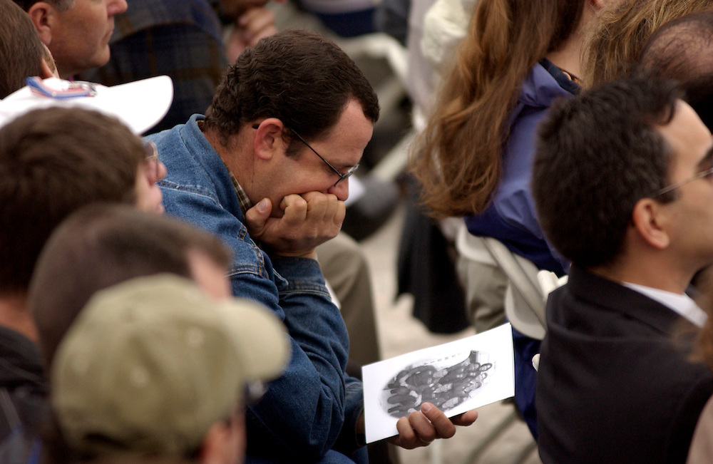 A NASA employee examines a photo of the Columbia crew during the STS-107 Columbia Crew Memorial Service at the Kennedy Space Center, Fla., February 7, 2003. The service was closed to the public. Space Shuttle Columbia was destroyed over Texas last week. (Photo by Matt Stroshane / Getty Images)