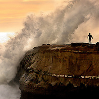 A surfer pauses before entering the lineup as a wave crashes at the tip of Lighthouse Point in Santa Cruz, California  in the late afternoon on Sunday January 10, 2010.